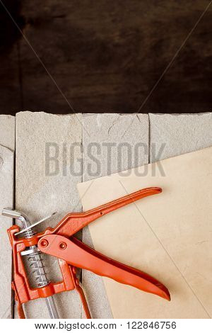 Metal Building Contractors Caulking Gun Tool on a stone background
