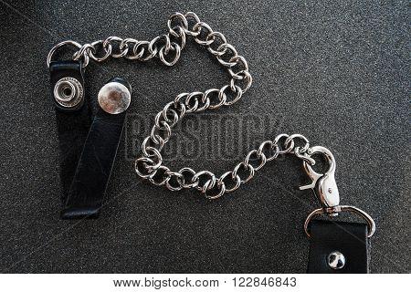 Wallet chains on black sandpaper texture background