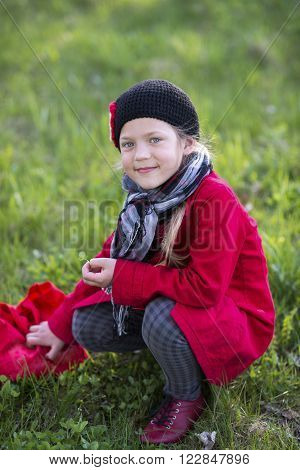 girl in red raincoat on the green spring time meadow