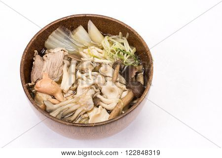 Various mushroom and vegetables, meat soup in wood bowl