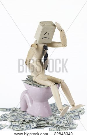 wooden businessman depress sitting on toilet bowl filled with cash