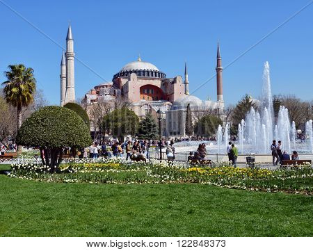 ISTANBUL, TURKEY - MARCH 22, 2014: People resting near the fountain against the Hagia Sophia. Hagia Sophia is one of the greatest surviving examples of Byzantine architecture