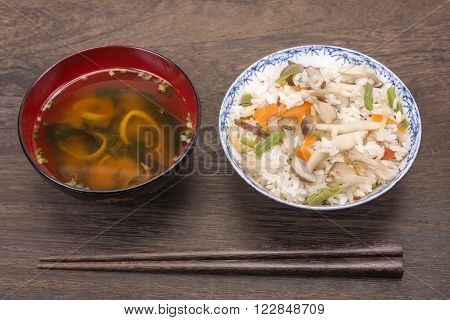 Japanese boiled rice seasoned with mixed mushrooms and miso soup, chopsticks