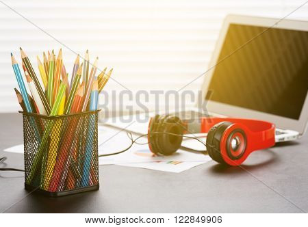 Office workplace with with laptop, reports, headphones and pencils on wooden desk table in front of window with blinds. Sunset light