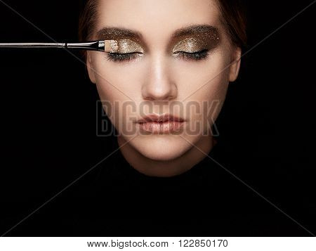 Makeup artist applies eye shadow. Beautiful woman face. Perfect makeup. Lips. Cosmetic Eyeshadow. Make-up detail. Eyeliner