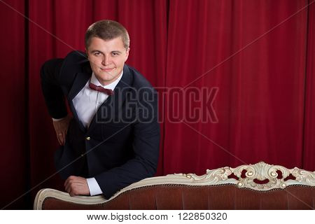 Happy young man in jacket and bowtie expressing positivity