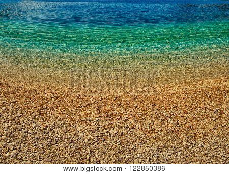 Abstract Background of Stone beach with clean transparent blue waters