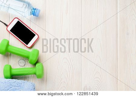 Fitness and diet concept background. Dumbbells, water bottle, smartphone and towel. Top view with copy space