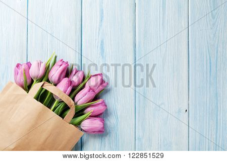 Fresh pink tulip flowers in paper bag on wooden table. Top view with copy space