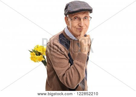 Romantic senior holding a bunch of flowers behind his back and gesturing silence isolated on white background