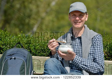 Man sitting on a bench and eating yogurt in a sunny day