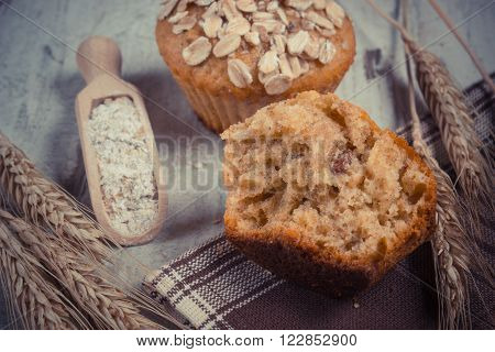 Vintage photo Fresh muffins with oatmeal baked with wholemeal flour rye flour and ears of rye grain concept of delicious healthy dessert or snack