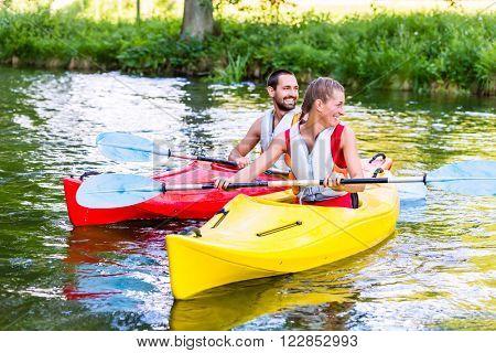 Friends going down river in sport canoe