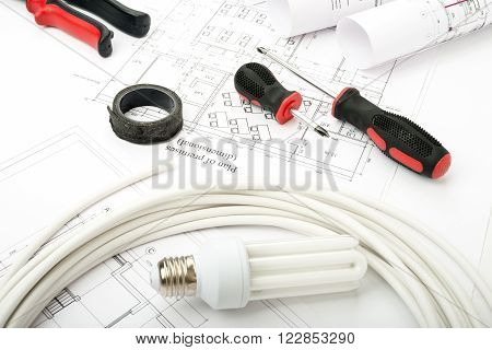 Architecture plan and rolls of blueprints with bulbs and screwdrivers. Building concept