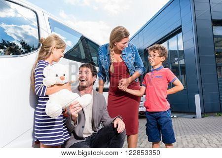 Family with children buying auto at car dealer standing in front of new van