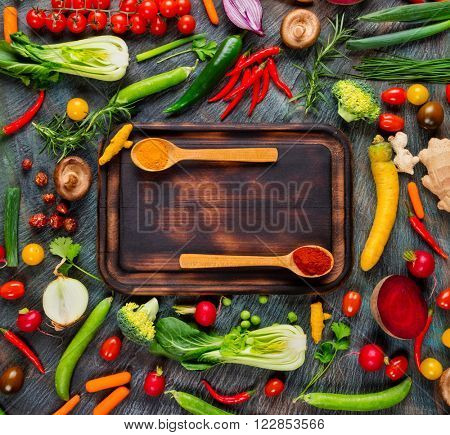 Collection of fresh vegetables placed on black stone with breadboard and wooden spoons