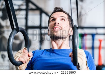 Man at rings doing fitness exercise in gym