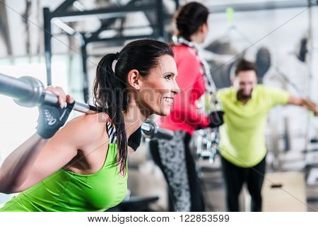 Woman in functional training lifting weights in gym