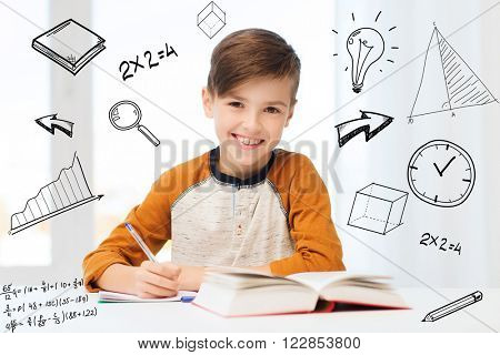 education, childhood, people, homework and school concept - smiling student boy with book writing to notebook at home over mathematical doodles