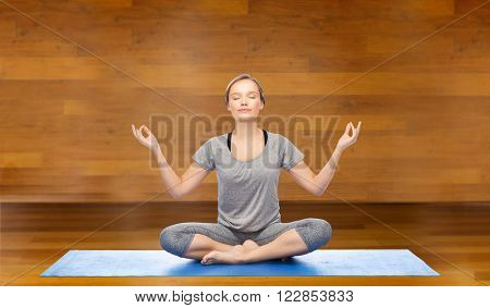 fitness, sport, people and healthy lifestyle concept - woman making yoga meditation in lotus pose on mat over wooden room background