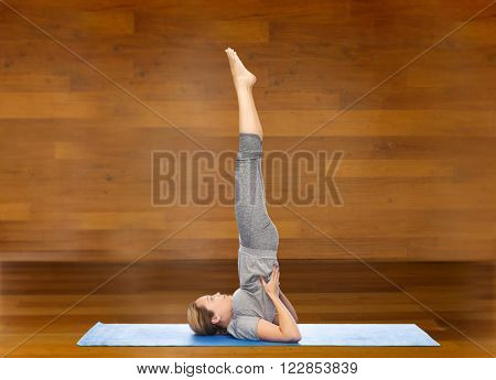 fitness, sport, people and healthy lifestyle concept - woman making yoga in shoulder stand pose on mat over wooden room background