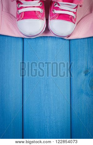 Clothing for newborn on blue boards baby shoes bodysuits concept of extending family and expecting for baby copy space for text or inscription
