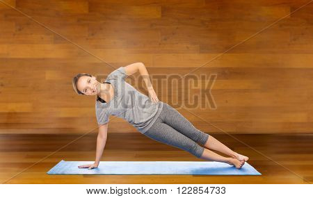 fitness, sport, people and healthy lifestyle concept - woman making yoga in side plank pose on mat over wooden room background