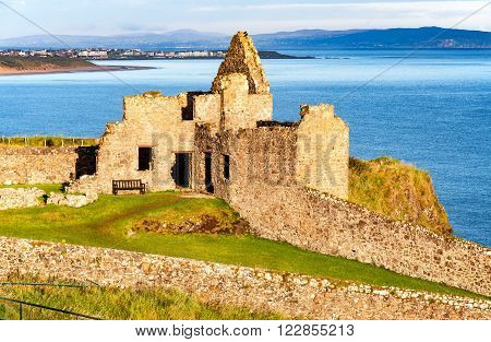 Fragment of ruins of Dunluce castle in County Antrim Northern Ireland UK with the far view of Portrush resort in the background