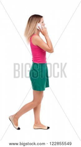 side view of a woman walking with a mobile phone. beautiful curly girl in motion.  backside view of person. Isolated over white background. The blonde in a green skirt and red sweater is left on phone