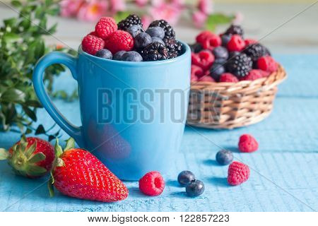 Berries spring fruits on blue wooden boards abstract still life