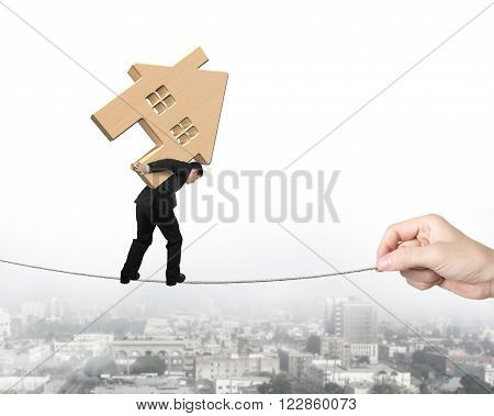 Man carrying wooden house and balancing on tightrope with hand pulling on cityscape background.