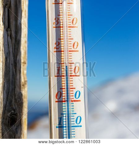 thermometer strapped on a post outside in the mountain shallow depth of field