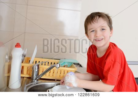 7 Year Old Boy Washes Dishes In The Kitchen