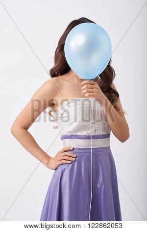 Shy girl hiding her face behind blue balloon