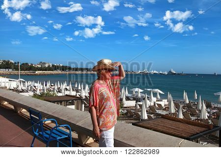 CANNES FRANCE - JULY 5 2015. Woman looking at the sea on Croisette promenade in Cannes France. Cannes located in the French Riviera. The city is famous for its Film Festival. CANNES FRANCE - JULY 5 2015