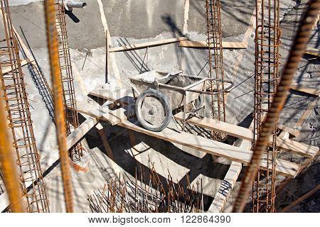 Barrow with concrete on construction site, tool