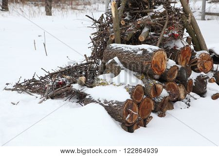 the logs on the snow-covered yard, snow on the logs