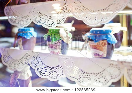 Jars with jam on a decorated openwork napkins showcase.