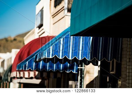 series of colorful canvas awnings shading small village shops