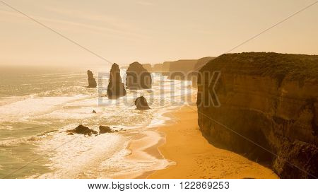 beautiful waves lapping on the beautiful rocky coast of large stones along the Great Ocean Road and unusual rock twelve apostles of Victoria and unusual yellow light of sunset Australia