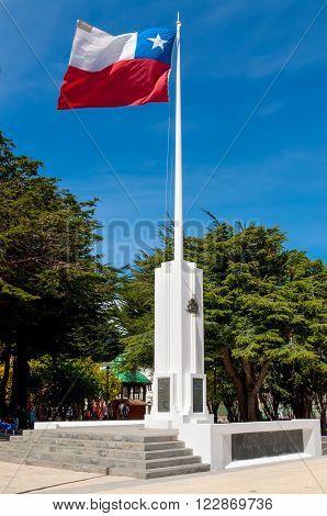 Punta Arenas Chile - December 9 2012: Chilean flag against blue sky in Plaza de Armas Punta Arenas Magallanes Region Chile.