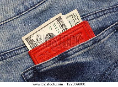 passport and dollars sticking out of a pocket of jeans