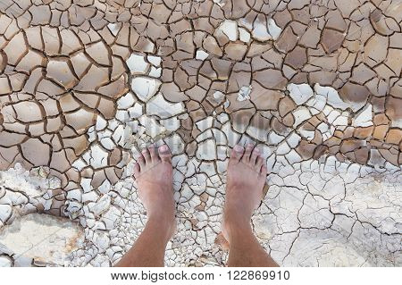 Close up Dirty bare feet on cracked land