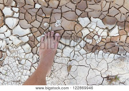 Close up Dirty bare foot on cracked land
