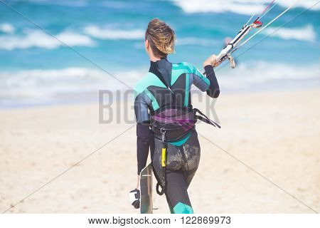 Sporty fit female kiteboarder walking in water with lunched kite and holding her board to start kiteboarding session.
