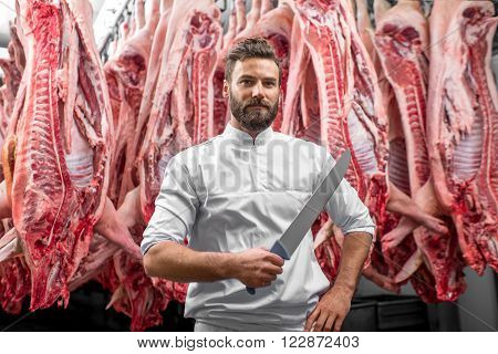 Portrait of a handsome butcher holding knife standing on the pork carcasses background at the meat manufacturing