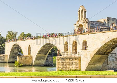 AVIGNON, FRANCE - AUGUST 15, 2013: Tourists walking on the Avignon bridge. The Pont Saint-Bénézet, known as Pont d'Avignon, was built between 1177 and 1185 and is classified as a World Heritage Site.