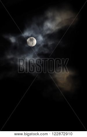 full moon in a cloudy night background fades to black with generous copy space vertical