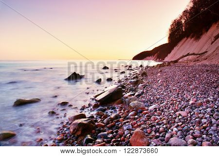 Blue Sea And Sky, Waves Break Off Stony Shore. Moment Before Sunrise