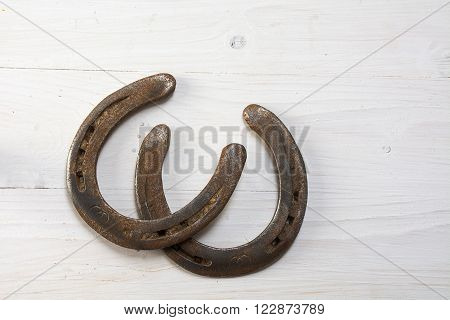 two old horseshoes used and with rust on white painted wood symbol for good luck background with copy space